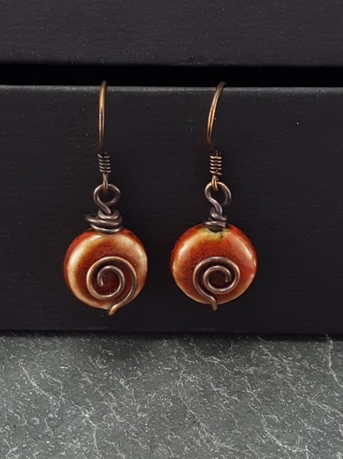 red earrings with copper spirals