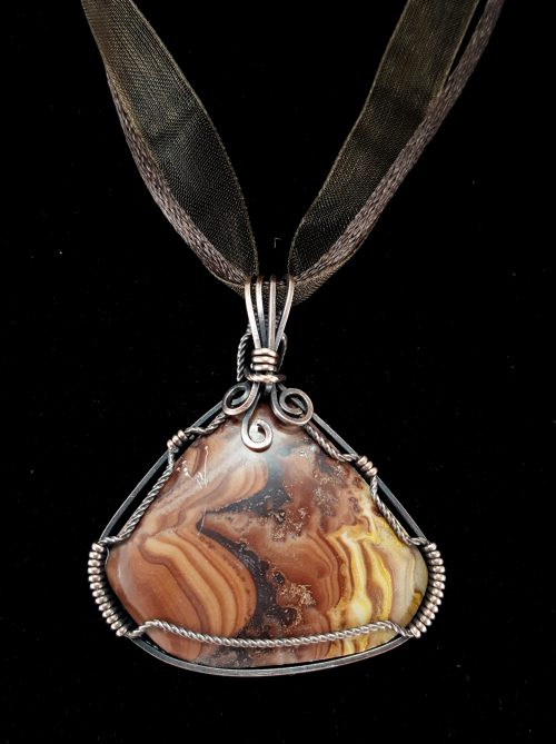 Picture Dolomite from Mexico wrapped in copper wire for this pendant setting. Extraversions pendants come with a free ribbon cord (as pictured, in dark brown or black). Black faux-leather cords, copper-toned chains, and light sterling silver chains are available for purchase as well.