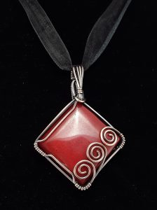 Red jade pendant in copper wire-wrapping with a trinity of spirals.