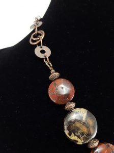 Red brecciated jasper necklace with copper-toned chain and spacer beads, and a toggle clasp in back. 20″