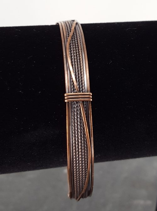 Copper wire bangle bracelet with surface wire ornamentation and spirals.