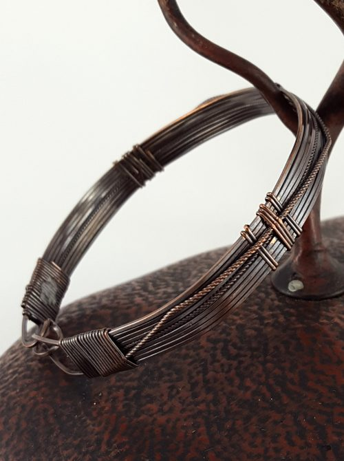 Copper wire bangle bracelet with surface ornamentation and built in clasp. 8″